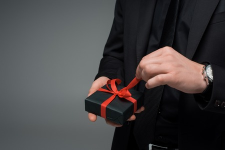 Partial view of male hand untying ribbon on gift box isolated on grey, international womens day concept