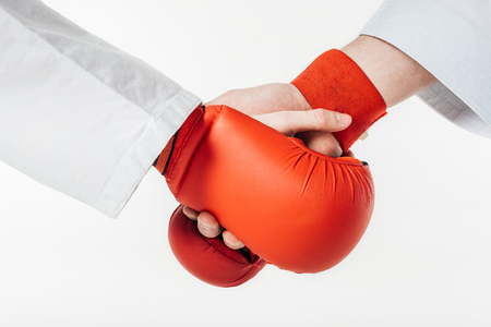 cropped image of karate fighters shaking hands in gloves isolated on white Stock Photo