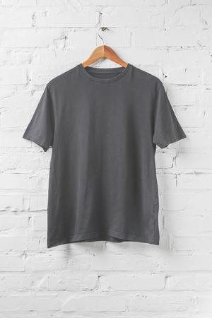 one dark grey shirt on hanger on white wall Stock Photo