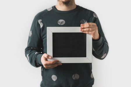 cropped image of man holding empty black board isolated on white Stock Photo
