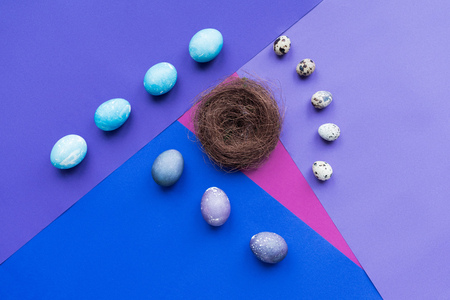 Composition of eggs and nest on background in purple tones