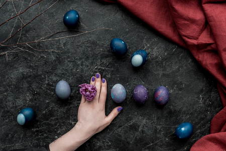 Female hand by Easter eggs on dark background