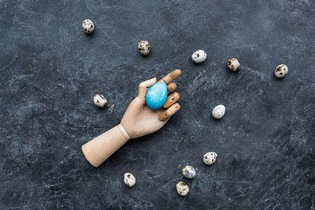 Quail eggs around mannequin hand with colored egg on dark background Banco de Imagens