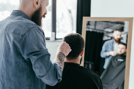 rear view of barber combing customer hair at barbershop