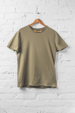 one brown shirt on hanger on white wall