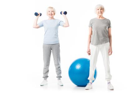 Smiling senior sportswomen with fitness ball and dumbbells isolated on white
