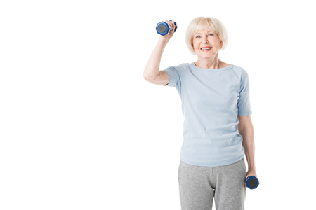 Smiling senior sportswoman with dumbbells in hands isolated on white