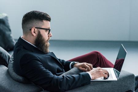 side view of focused stylish businessman using laptop Banco de Imagens