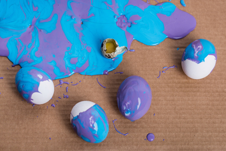 Broken quail egg and chicken eggs in paint on cardboard background