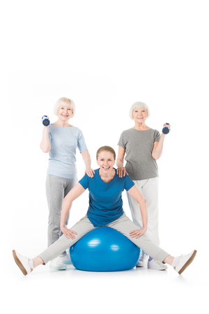 Three sportswomen with dumbbells and fitness ball isolated on white