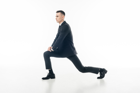 businessman stretching legs in suit isolated on white Zdjęcie Seryjne