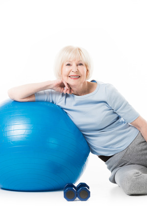 Smiling senior sportswoman with fitness ball and dumbbells isolated on white Stock Photo