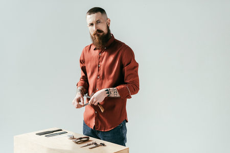 bearded handsome barber near table with equipment isolated on white