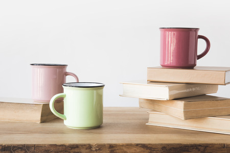 three colored cups and books on wooden table on white