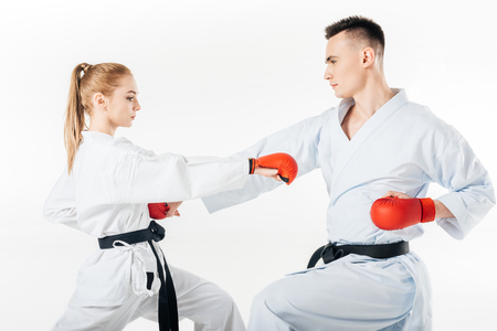 side view of karate fighters training in kimono and red gloves isolated on white
