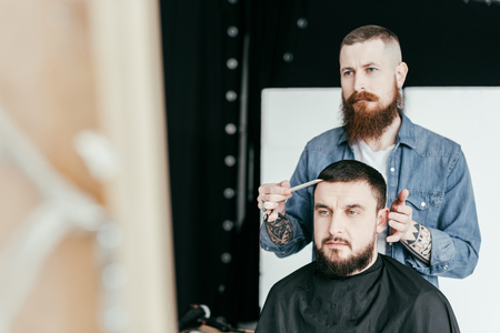 barber looking at customer haircut in mirror at barbershop Stock Photo