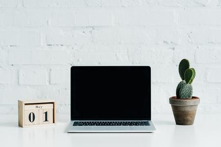 Holzkalender mit Datum 1. Mai, Laptop mit leerem Bildschirm und Kaktuspflanze