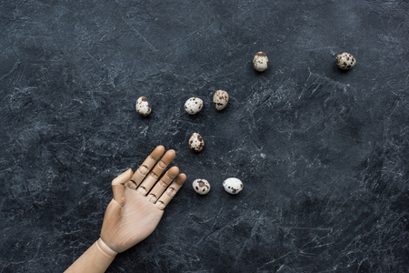 Mannequin hand with quail eggs on dark background 스톡 콘텐츠