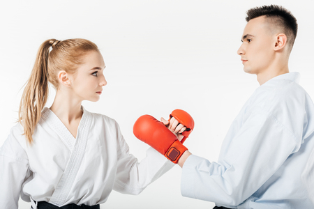 side view of karate fighters touching with gloves isolated on white