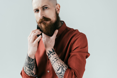 tattooed man combing beard and looking at camera isolated on white