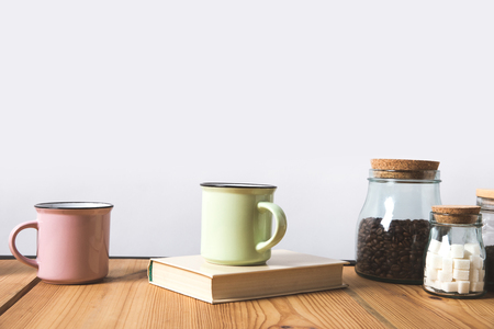 cups, book and glass bottles with coffee beans and refined sugar on table on white