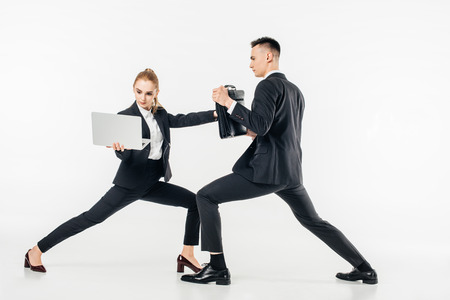 businesswoman holding laptop and kicking businessman in bag isolated on white