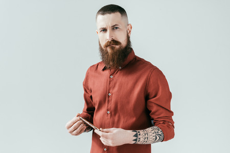 bearded handsome barber holding razor and looking at camera isolated on white