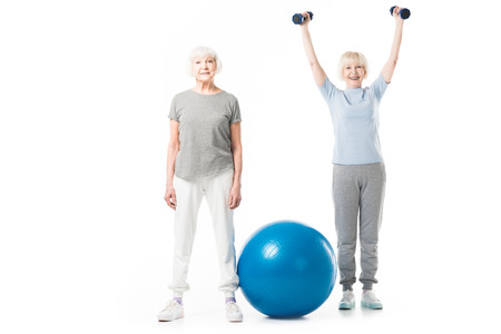Senior sportswomen with fitness ball and dumbbells isolated on white