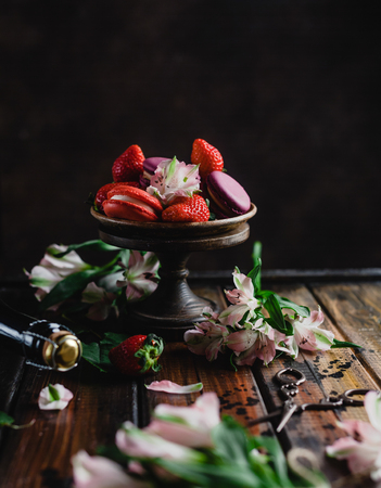 bowl with macarons and strawberries on wooden table with flowers and champagne bottle and scissors, Stok Fotoğraf - 111802065