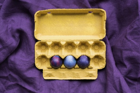 Three Easter eggs in carton on textile background