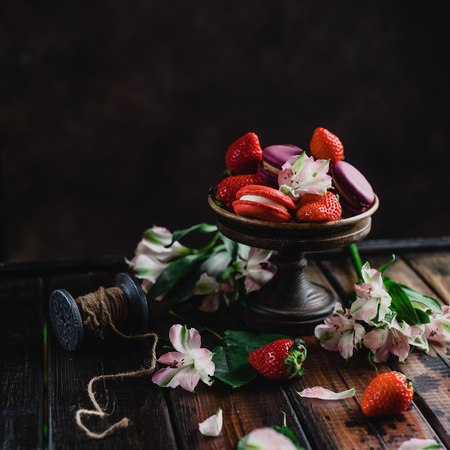 bowl with sweets macarons and strawberries on wooden table with flowers