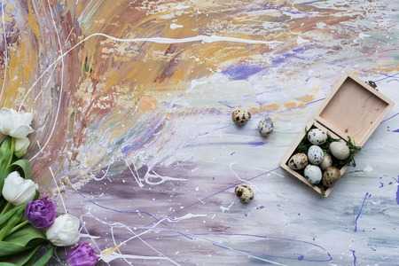Quail eggs in box and tulips on stained background