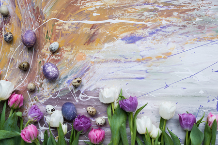 Colored chicken and quail eggs and tulips on stained background