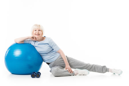 Senior sportswoman with fitness ball and dumbbells isolated on white