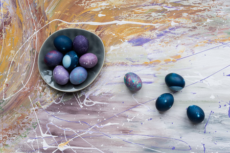 Easter eggs in bowl and on stained background