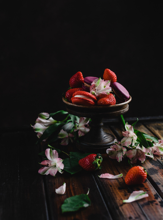 bowl with macarons and strawberries on wooden table with flowers