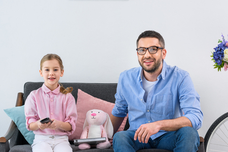 smiling family resting on sofa watching tv at home