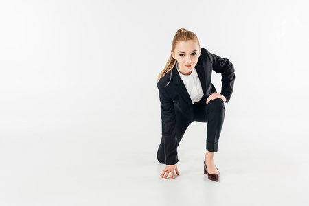 businesswoman standing on knee and looking at camera in suit isolated on white