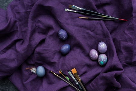 Easter eggs and brushes on textile background