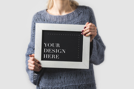 cropped image of woman holding black board with words your design here isolated on white