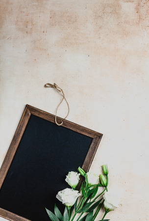 top view of wooden frame with eustoma flowers on shabby background