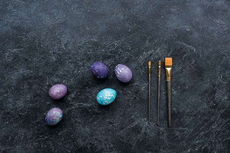 Easter eggs and brushes on dark background