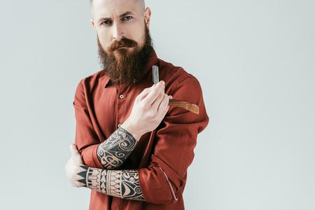 bearded serious barber holding razor isolated on white