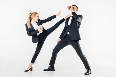 businesswoman in suit kicking businessman with coffee to go isolated on white