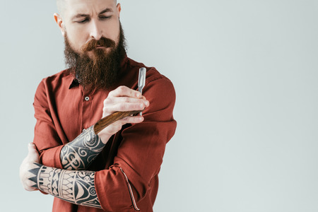 bearded handsome barber looking at razor isolated on white