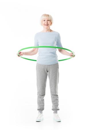 Smiling enior sportswoman doing hula hoop exercise isolated on white