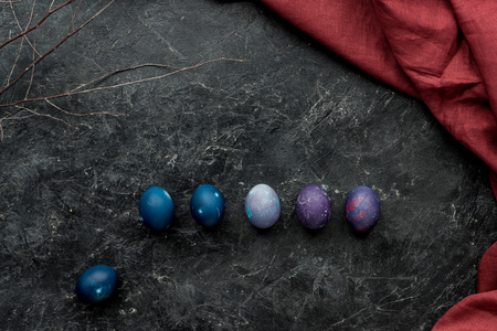 Row of colored eggs on dark background