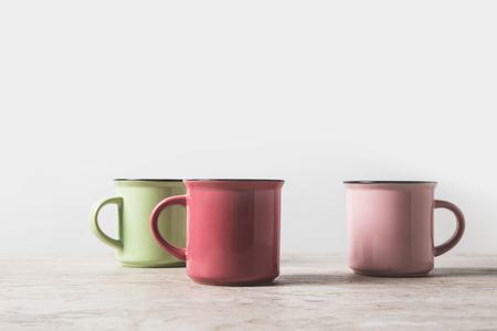 three colored cups on marble table on white Stock Photo