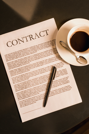 top view of contract and cup of coffee on dark tabletop Stock fotó