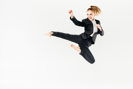 businesswoman screaming, jumping and performing kick in suit isolated on white